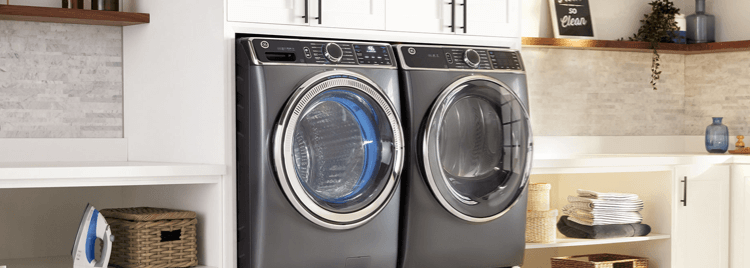 Two GE Front Load Washing Machines in a white laundry room