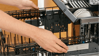 Person troubleshooting ge dishwasher