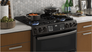 GE Gas Oven with cookware cooking dishes on the stove