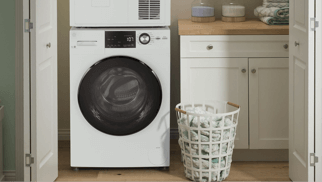White GE Front load washing machine next to a white laundry basket